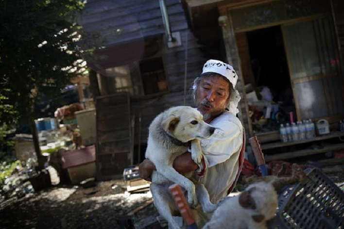 Keigo Sakamoto, holds Atom one of his 21 dogs and over 500 animals he keeps at his home in the exclusion zone near Naraha in Fukushima prefecture