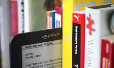 A Kindle alongside some paper books